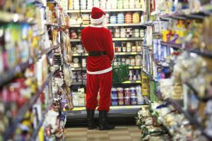 Man dressed as Santa Claus standing in supermarket, rear view