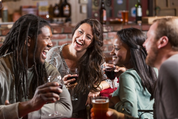 Multiracial group of friends drinking at restaurant bar