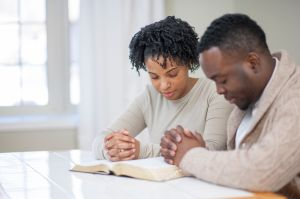 Religious Ethnic Couple Praying with a Bible