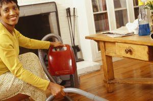 Woman vacuuming living room floor, portrait