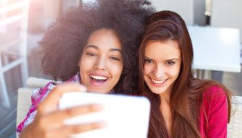 Two smiling female friends driniking coffee and taking selfie
