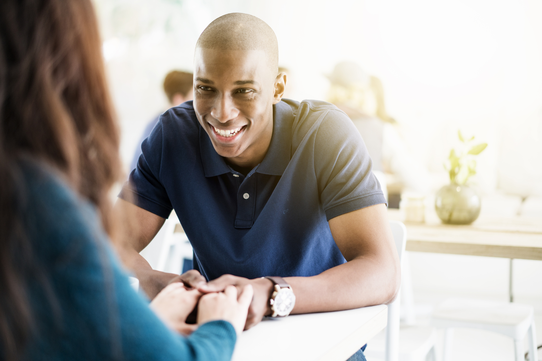 Smiling young man holding hands of woman in cafe