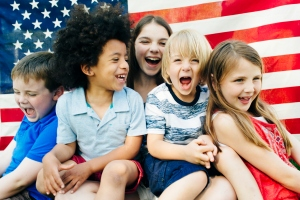 Group of laughing children (2-3, 4-5, 6-7) in front of American flag