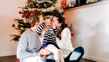 Parents kissing daughter while sitting against Christmas tree at home