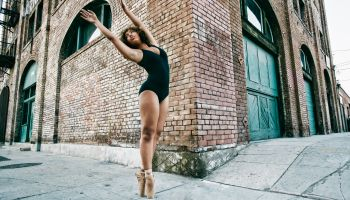 Mixed race ballet dancer on sidewalk in city
