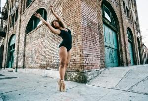 Mixed race ballet dancer on sidewalk in city
