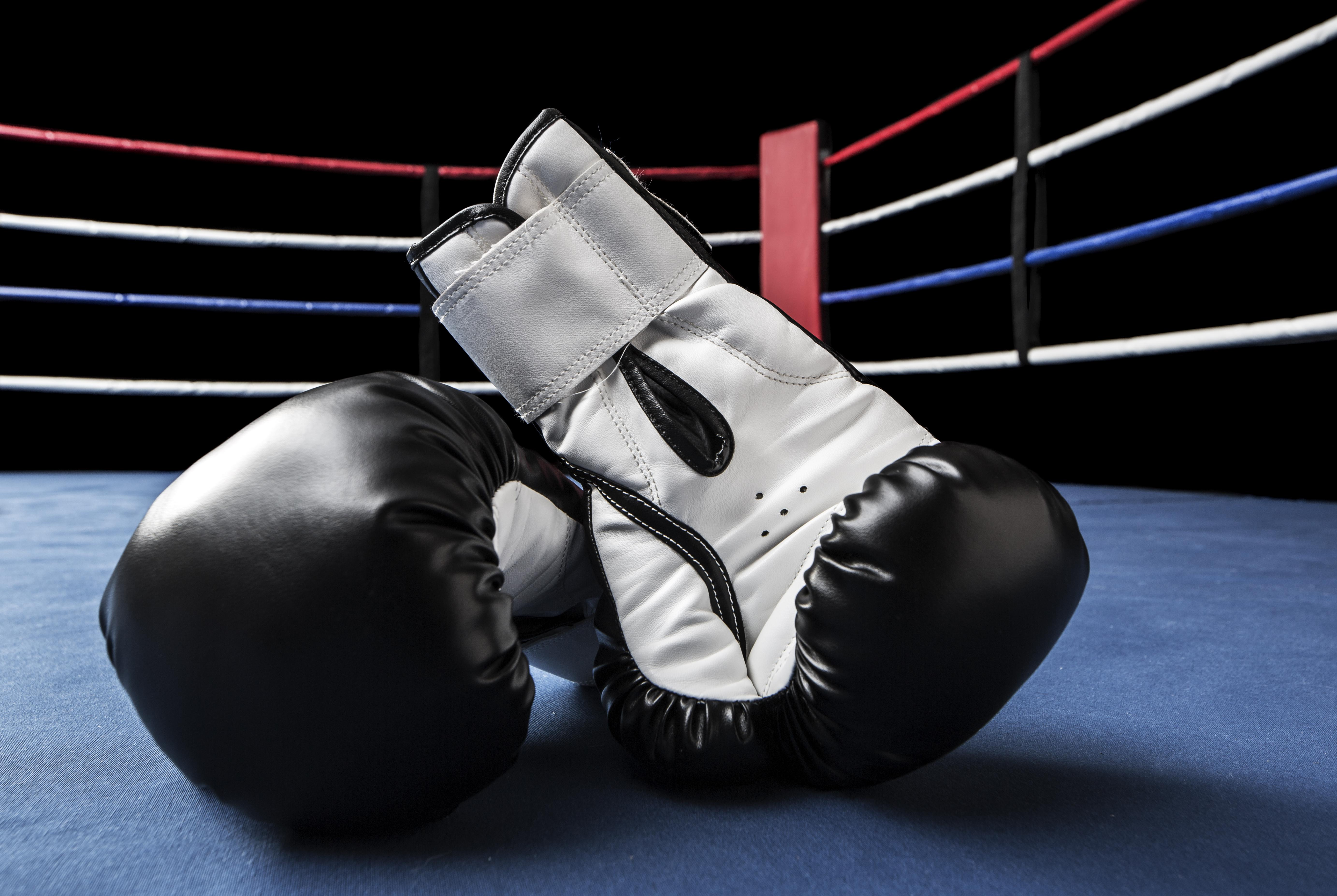 Black boxing gloves inside ring