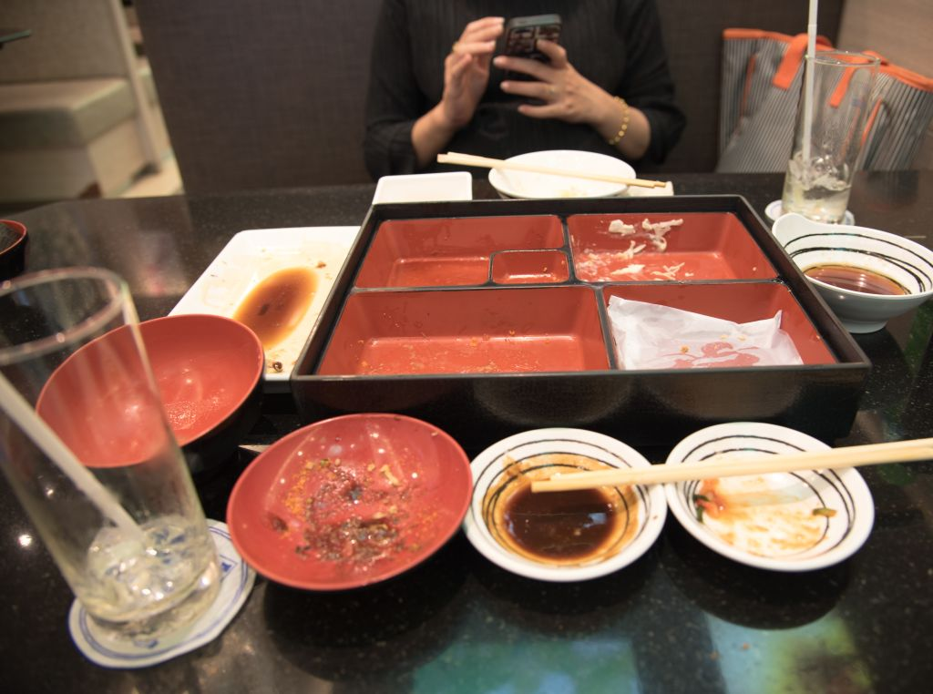 Midsection Of Woman Using Mobile Phone By Empty Containers On Table