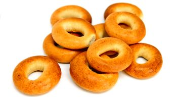 Stack of a golden brown bagels in a variety of flavors.