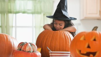 Hispanic girl in witch's hat carving a pumpkin