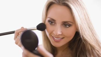 Woman applying blush using compact mirror