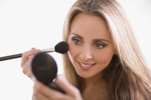Woman applying blush using compact mirror