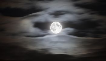 Full moon on a cloudy night sky